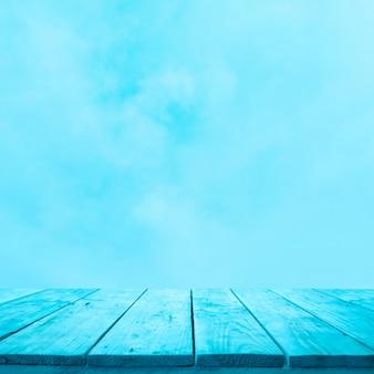 부드러운 하늘 배경에 파란색 나무 테이블 상단의 빈. 몽타주 제품 디스플레이