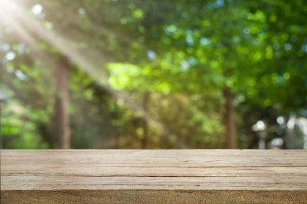 日光のある庭からの新鮮な緑の抽象画のぼかしに木製のテーブルトップの空。