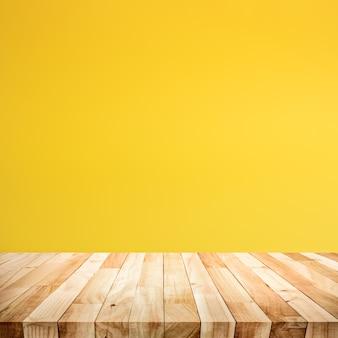 노란색 파스텔 컬러 배경에 나무 테이블 상단의 빈