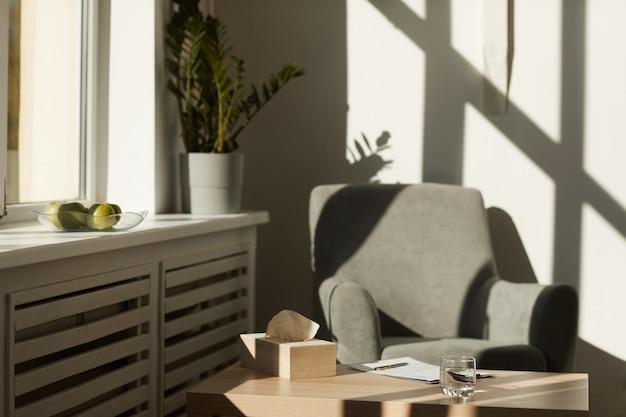 ナプキンと書類を備えたアームチェアとテーブルを備えた心理学者の空のオフィス