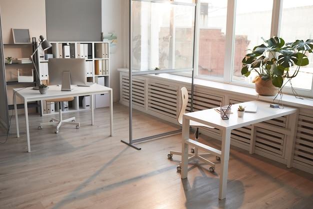 仕事を手配するテーブルとコンピューターを備えた空のオフィス