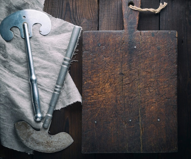 Empty old brown cutting board and two iron knives