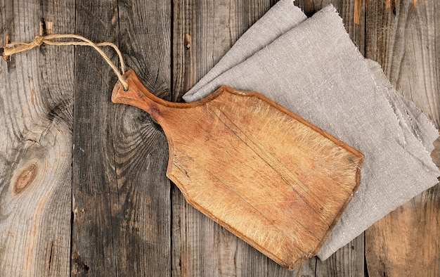 Empty old brown wooden cutting board with handle