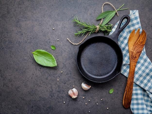 Пустая старая чугунная сковородка на фоне темного камня.