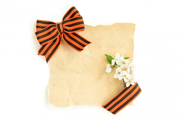 Empty old paper card with st. george ribbon bow and flowers isolated on white background.