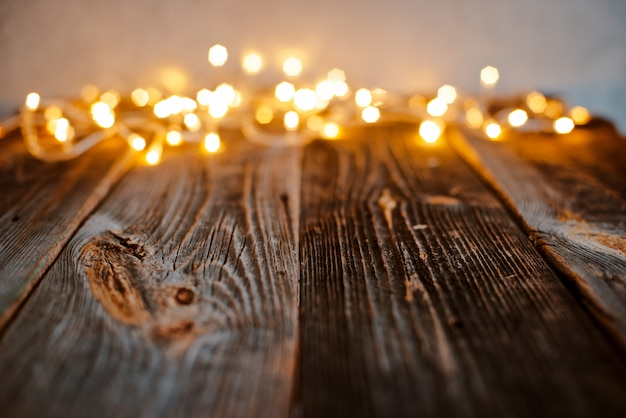 Empty old wooden countertop with blurred gold bokeh christmas lights abstract .