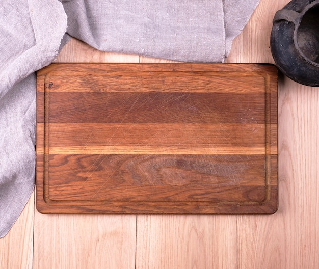 Empty old wooden kitchen cutting board and a gray towel