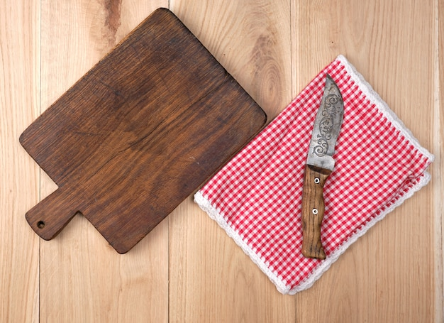 Empty old wooden kitchen cutting board and knife on table