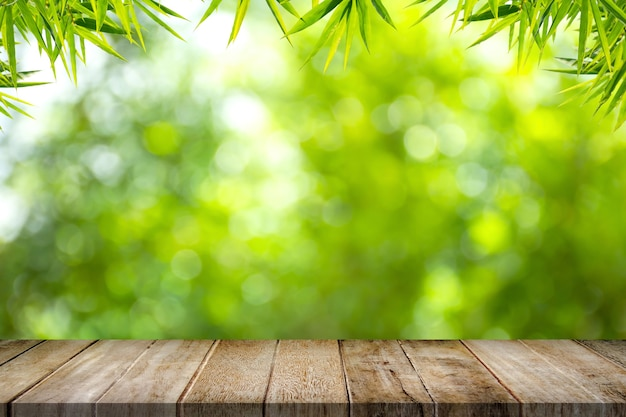 Empty old wooden table top with bamboo leaves frame on blurred greenery background in garden
