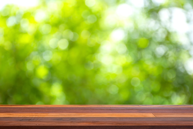 庭のぼやけた緑の背景と空の古い木製のテーブルトップ