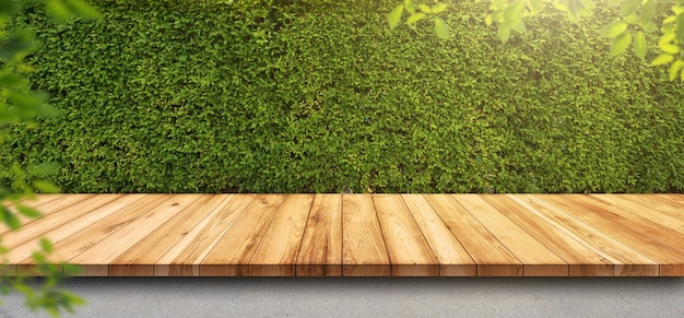 Empty old wooden table with green leaves wall