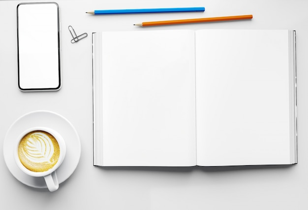 Empty open book and blank and empty screen smart phone with coffee cup and pencil on table