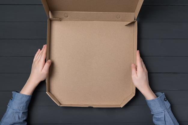 子供たちの手でピザの空のオープンボックス。黒の背景。上面図。スペースをコピーします。