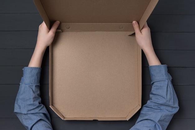 子供たちの手でピザの空のオープンボックス。黒い表面。上面図。コピースペース。