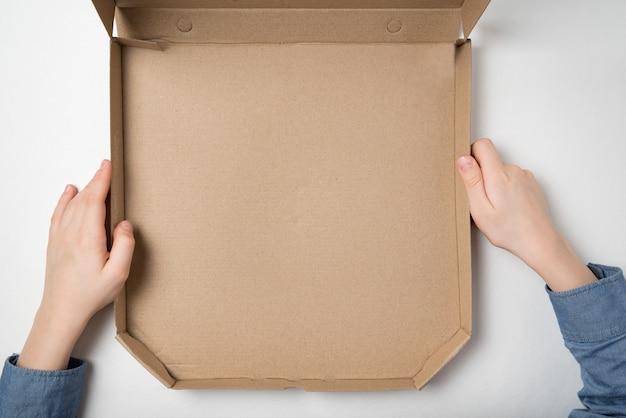 Опорожните открытую коробку пиццы в руках детей на белой предпосылке.