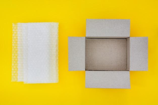 Empty open brown paper cardboard box and translucent white plastic bubble wrap