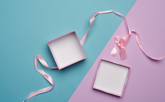 Empty open cardboard box and pink ribbon with bow