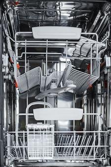 Empty open dishwasher ready for washing