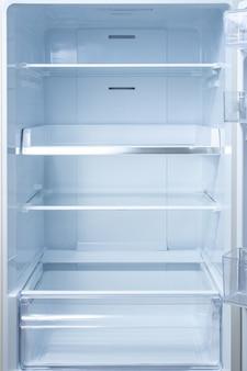 Пустой открытый холодильник с полками