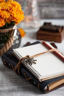 Пустой открытый блокнот и оранжевые цветы хризантемы на деревенском столе.