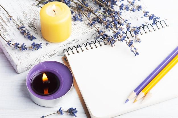 乾燥したラベンダーの花とキャンドルで空の開いたノートブック