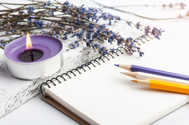 Empty open notebook with dry lavender flowers. aromatherapy arrangement, zen still life with lit candles