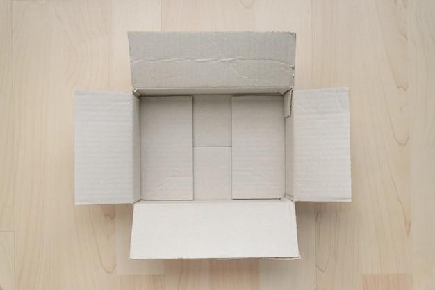 Пустая открытая прямоугольная картонная коробка на дереве.