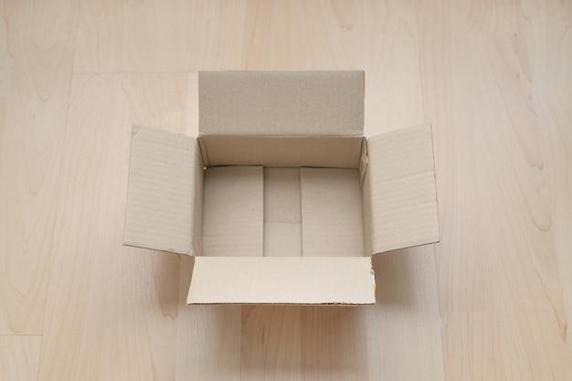Empty open rectangular cardboard box on wood.