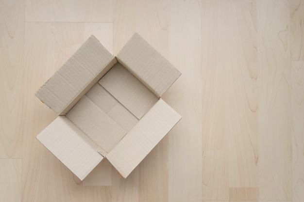 Empty open rectangular cardboard box on wood.