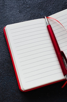 Empty open red notebook with red pen on dark background