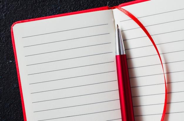 Опорожните открытую красную тетрадь с красной ручкой на темной предпосылке. чистый лист бумаги для текста.