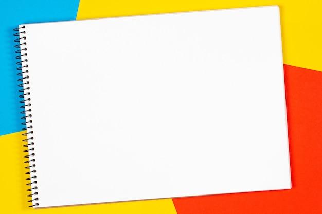 Пустой открытый белый альбом для рисования с пространством для текста на геометрическом минимуме.