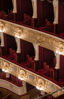 Пустые уровни балкона оперного театра с красными стульями