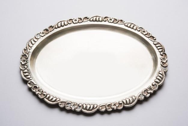 흰색 표면 위에 격리된 장식 테두리가 있는 비어 있거나 빈 은제품 또는 타원형 은판, 선택적 초점