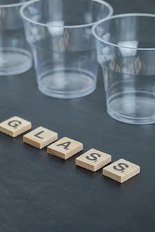 Пустые или наполненные стаканы для воды на черной поверхности