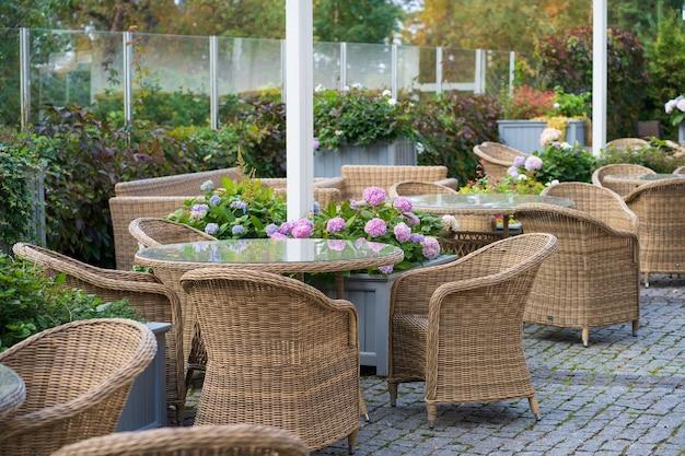 Пустая открытая терраса кафе с плетеной мебелью и растущими цветами в горшке для летних развлечений