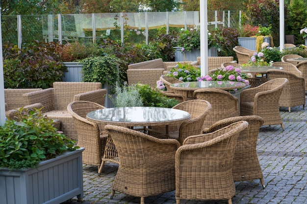 Empty outdoor cafe terrace with wicker furniture and growing flowers in pot for summer entertainment
