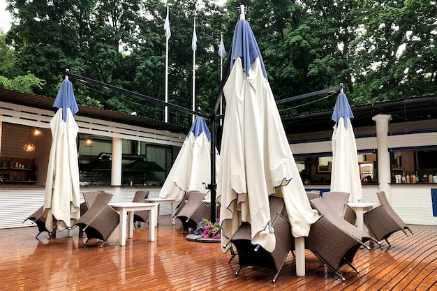 Empty outdoor cafe with closed umbrellas and stacked furniture due to the weather