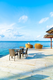 Empty outdoor patio deck and chair with blue ocean in maldives