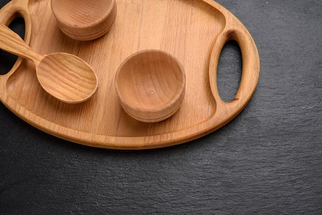 Empty oval brown wooden tray board on a black background, top view