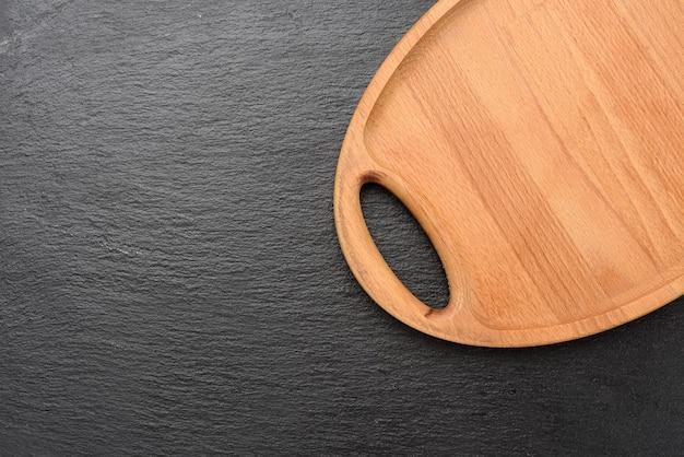 Пустой овальный коричневый деревянный поднос на черном фоне, вид сверху