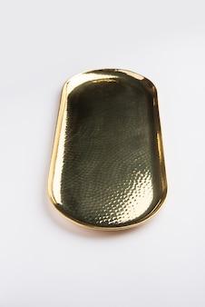 흰색 표면 위에 황동, 피탈 또는 금으로 구성된 빈 타원형 또는 둥근 모양의 탈리 또는 플레이트