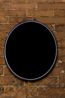 Empty oval sign with copy space on the old brick wall