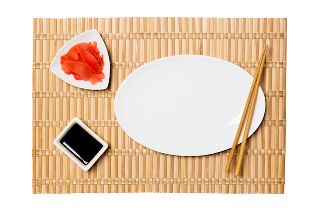 Empty oval white plate for sushi with chopsticks, ginger and soy sauce on bamboo mat