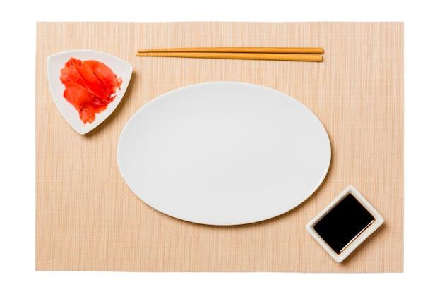 Пустая овальная белая тарелка с палочками для суши, имбирем и соевым соусом на коричневой поверхности коврика для суши
