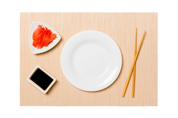 Empty oval white plate with chopsticks for sushi, ginger and soy sauce on brown sushi mat background