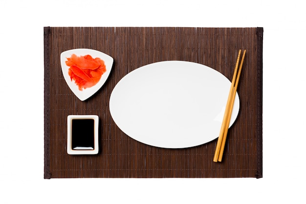 Empty oval white plate with chopsticks for sushi, ginger and soy sauce on dark bamboo mat background. top view with copyspace