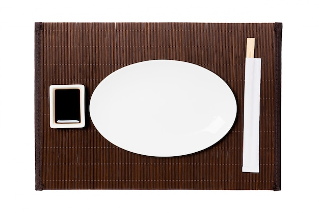 Empty oval white plate with chopsticks for sushi and soy sauce on dark bamboo mat background