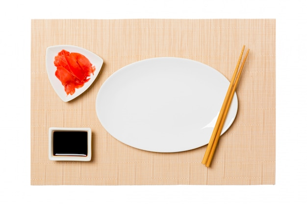 Empty oval white plate with chopsticks for sushi and soy sauce, ginger on brown sushi mat . top view with copyspace