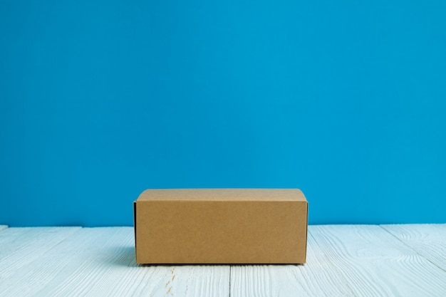 Empty package brown cardboard box or tray on bright white wooden table with blue wall background.